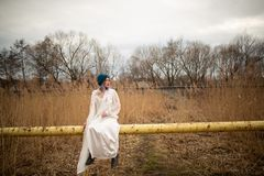 Ein junges M?dchen gekleidet in einem wei?en langen Kleid, sitzend auf einem Rohr, nahe einem Weizenfeld stockfoto
