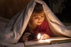 Ein junges Mädchen, das ein Buch unter den Abdeckungen mit einer Taschenlampe liest Lizenzfreie Stockbilder