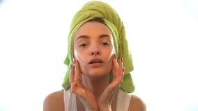 Ein junges Mädchen mit einem Tuch auf ihrer Hauptweichheit verursacht Creme auf Gesicht stock video