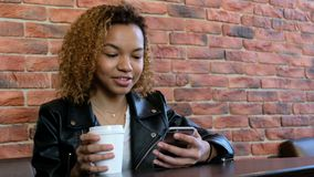 Ein junges modernes schönes afro-amerikanisches Mädchen, das eine weiße Schale und ein Telefon hält und etwas sagt Triebvideo von stock video footage