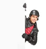 Ein junges motorcycler, das ein weißes Panel behing aufwirft Stockfotos