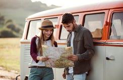 Ein junges Paar auf einem roadtrip durch die Landschaft, eine Karte betrachtend lizenzfreies stockbild