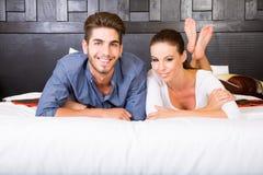 Ein junges Paar, das auf dem Bett in einem asiatischen Arthotelzimmer liegt Lizenzfreie Stockfotos