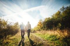 Ein junges Paar, das draußen Händchenhalten geht Lizenzfreies Stockfoto
