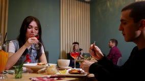 Ein junges Paar, das durch Tabelle in einem Café sitzt Essen und Trinken stock video footage