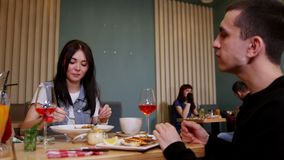 Ein junges Paar, das durch Tabelle in einem Café sitzt Essen von Meeresfrüchten und von Teigwaren stock video