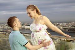 Ein junges Paar, das ein Baby erwartet. Eine junge schwangere Frau, die auf das Dach mit ihrem Ehemann geht. Lizenzfreie Stockbilder