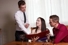 Ein junges Paar, das ein Menü liest Stockbild