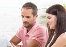Ein junges Paar, das eine Tablette betrachtet Stockfotografie