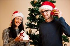 Ein junges Paar, das vor dem Weihnachtsbaum und dem givin steht Stockfotografie