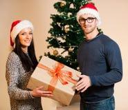 Ein junges Paar, das vor dem Weihnachtsbaum und dem givin steht Stockbilder