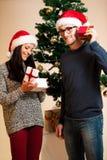 Ein junges Paar, das vor dem Weihnachtsbaum und dem givin steht Lizenzfreie Stockbilder