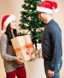 Ein junges Paar, das vor dem Weihnachtsbaum und dem givin steht Stockbild