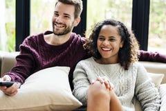 Ein junges Paar, das zusammen eine Fernsehshow aufpasst lizenzfreie stockfotos