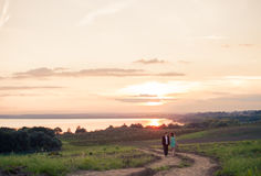 Ein junges Paar in der Liebe im Freien bei dem Sonnenuntergang Lizenzfreies Stockbild