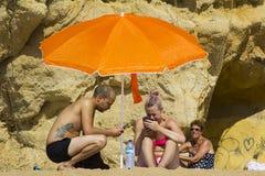Ein junges Paar am Feiertag, der ihre Handys in der Sonne auf dem Strand in Albuferia, Portugal betrachtet Stockfoto