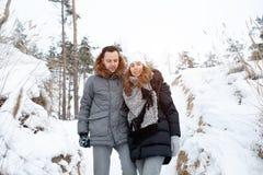 Ein junges Paar, ein Mann und eine Frau gehen in eine Winterfreizeit Wald des Winters schneebedeckte stockbild