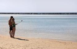 Ein junges Paar nimmt ein selfie gegen das Meer lizenzfreie stockfotos