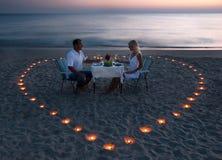 Ein junges Paar teilen ein romantisches Abendessen auf dem Strand stockfotografie