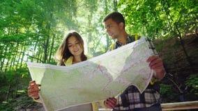 Ein junges Paar von den Touristen, die eine Karte betrachten Sie stehen in den Strahlen der Sonne im Wald nahe dem Wasserfall stock video