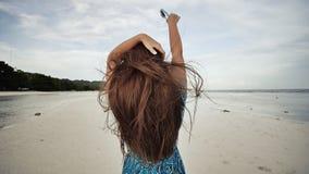 Ein junges russisches Mädchen mit glücklichen Gefühlen geht entlang den Strand und wirft vor der Kamera auf Das Mädchen ist stock video footage