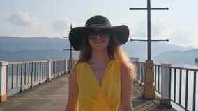 Ein junges schönes Mädchen in einem gelben Kleid geht entlang den Pier Sea Ozean stock footage