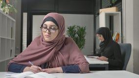 Ein junges schönes Mädchen in einem Punkt und in einem rosa hijab schreibt weg auf Arabisch Arabische Frauen in den Büro 60 fps stock footage