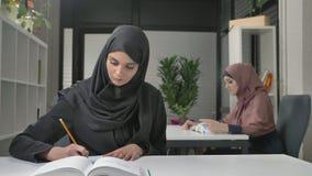 Ein junges schönes Mädchen in einem Punkt und in einem schwarzen hijab schreibt weg auf Arabisch Arabische Frauen in den Büro 60  stock footage