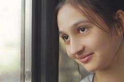 Ein junges schönes Mädchen schaut heraus das Fenster und lächelt stockfoto