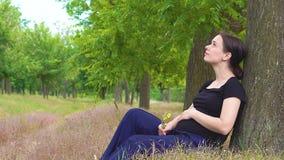 Ein junges, schönes, schwangeres Mädchen sitzt unter einem Baum in einem schwarzen T-Shirt stock video footage