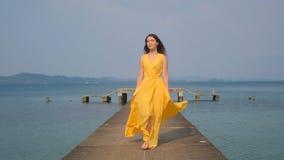 Ein junges sch?nes M?dchen in einem gelben Kleid geht entlang den Pier Sea Ozean stock video