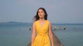 Ein junges sch?nes M?dchen in einem gelben Kleid geht entlang den Pier Sea Ozean stock video footage