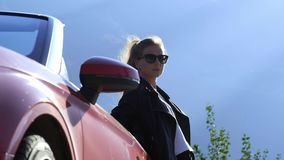 Ein junges stilvolles brunette Mädchen in einer Lederjacke und in der Sonnenbrille steht nahe bei einem roten Kabriolett stock video