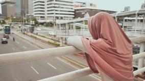 Ein junges, trauriges moslemisches Mädchen steht auf einer Brücke über dem Verkehr in im Stadtzentrum gelegenem Jakarta indonesie stock video footage