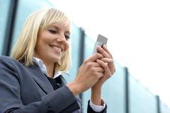 Ein junges und glückliches blondes auf dem Handy Stockbild