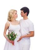 Ein junges und reizendes kaukasisches Paar, das Blumen hält Stockfotografie