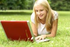 Ein junges und schönes Mädchen liegt auf dem Gras Lizenzfreie Stockfotografie
