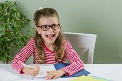 Ein Junior-schoolgirll in den Gläsern, die etwas in Schreibheft a schreiben Stockbilder