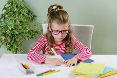 Ein Juniorschulmädchen mit Gläsern schreibt etwas mit ihrer linken Hand in das Notizbuch und sitzt am Tisch Das Kind ist links Lizenzfreies Stockfoto