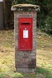 Ein königlicher Postbriefkasten in einer Ziegelsteinsäule auf dem Grün stockbild