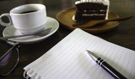 Ein köstlicher Kuchen mit einem Kaffee und dem Taschenbuch lizenzfreie stockbilder