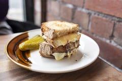 Ein köstliches Schmelzenkäsesandwich mit einer Gurke auf einer weißen und braunen Platte lizenzfreies stockbild