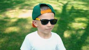 Ein kühler Junge mit 5-Jährigen in der Sonnenbrille steht im Sommerpark und fängt an, über jemand, die wirklichen Gefühle zu lach stock footage
