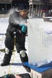 Ein Künstler, der einen Block des Eises schnitzt Lizenzfreie Stockbilder