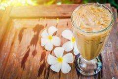 Ein Kaffeeglas im Garten mit weißem Plumeria blüht auf Holz stockbild