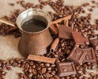 Ein Kaffeetopf, Röstkaffeebohnen, Zimtstangen und Stücke Schokolade auf einem Sackleinen Stockfotos