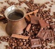 Ein Kaffeetopf, Röstkaffeebohnen, Zimtstangen und Stücke Schokolade auf einem Sackleinen Lizenzfreie Stockfotos