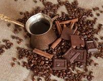 Ein Kaffeetopf, Röstkaffeebohnen, Zimtstangen und Stücke Schokolade auf einem Sackleinen Lizenzfreie Stockbilder