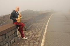 Ein kahler Mann spielt auf einem Goldaltsaxophon auf dem Straßenrand, wieder lizenzfreies stockbild