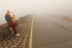 Ein kahler Mann spielt auf einem Goldaltsaxophon auf dem Straßenrand, wieder stockfotografie